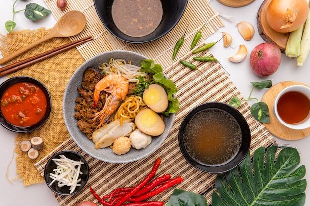 Gli hokkien mee vengono conditi nel lardo di maiale e serviti con polpette di gamberi