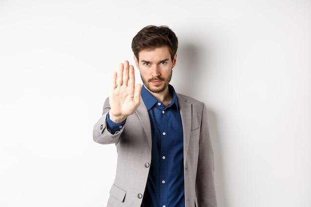 Aspetta lì. un uomo d'affari serio in tuta allunga la mano e dice di fermarsi, aggrottando le sopracciglia e guardando fiducioso, disapprovare l'azione, proibire qualcosa di brutto, in piedi su sfondo bianco.