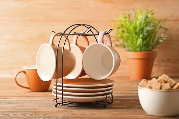 Supporto con tazze e piattini sul tavolo della cucina