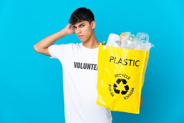 In possesso di un sacchetto pieno di bottiglie di plastica da riciclare su sfondo blu avendo dubbi