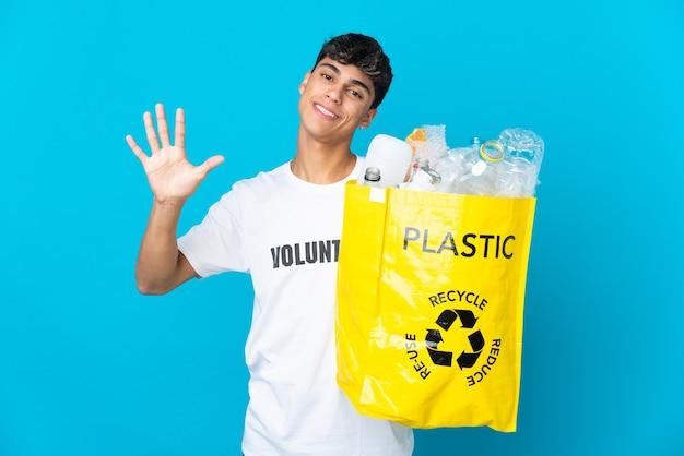 In possesso di un sacchetto pieno di bottiglie di plastica da riciclare sul blu contando cinque con le dita