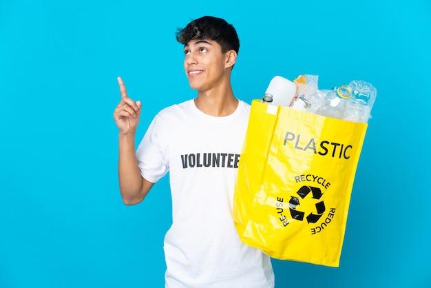 Tenendo in mano una borsa piena di bottiglie di plastica da riciclare sul blu che indica una grande idea