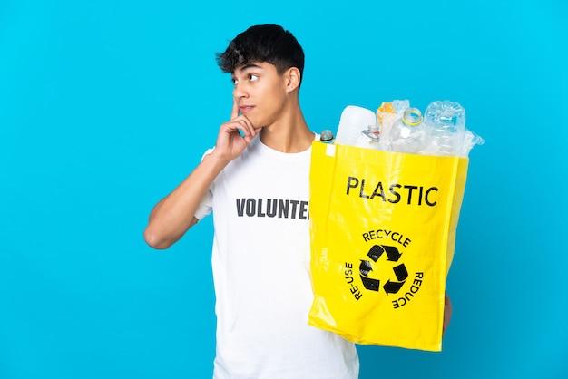 In possesso di un sacchetto pieno di bottiglie di plastica da riciclare sul blu pensando a un'idea mentre guarda in alto