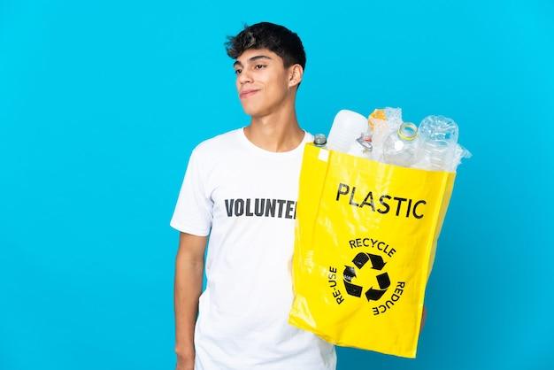 In possesso di un sacchetto pieno di bottiglie di plastica da riciclare sul blu pensando a un'idea mentre si guarda in alto