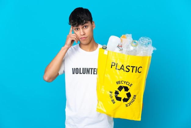Tenendo una borsa piena di bottiglie di plastica da riciclare sul muro blu pensando a un'idea