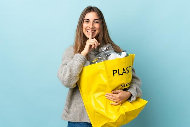 Tenendo un sacchetto pieno di bottiglie di plastica per riciclare isolato blu facendo il gesto del silenzio