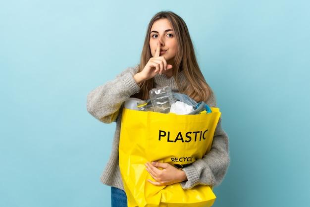 Tenendo una borsa piena di bottiglie di plastica per riciclare il gesto di silenzio facendo blu isolato