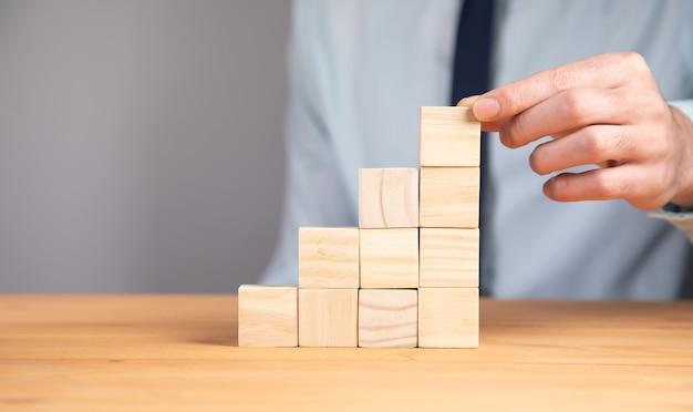 Tenendo i cubi di blocco di legno vuoti sul fondo della tavola, priorità bassa di concetto di affari