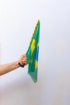 Tenendo la bandiera del brasile isolati su sfondo bianco. bandiera e immagine del concetto di festa dell'indipendenza.