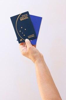 Tenendo il passaporto del brasile e la carta di lavoro isolati su fondo bianco. immagine di concetto.
