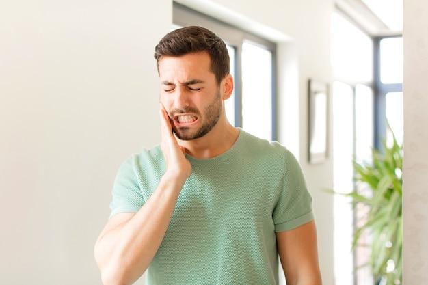 Tenere la guancia e soffrire di un doloroso mal di denti, sentirsi male, miserabile e infelice, cercare un dentista