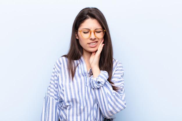 Con la guancia in mano e il mal di denti doloroso, sentirsi male, miserabile e infelice, alla ricerca di un dentista
