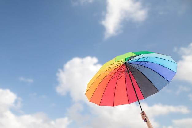 Tenendo l'ombrello colorato per la protezione dai raggi uv.