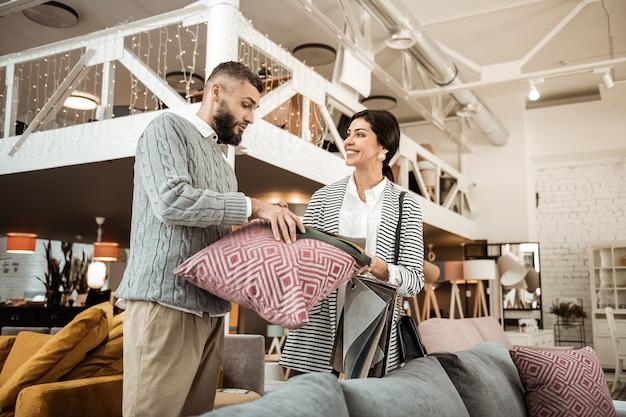 Tenendo il cuscino del divano. coppia curiosa confrontando i colori dei materiali durante la scelta dei mobili per il nuovo soggiorno