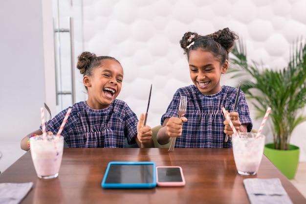 Tenendo le posate. due figlie ridenti divertenti che tengono le posate mentre aspettano il cibo che si siede nella caffetteria