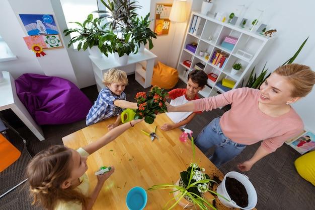 Tenendo il vaso di fiori. vista dall'alto dell'insegnante di ecologia e tre alunni che tengono un vaso di fiori con fiori rossi