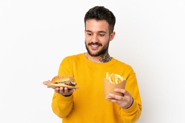 Tenendo patatine fritte e cheeseburger su sfondo isolato