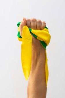 Tenendo i nastri verdi e gialli della bandiera del brasile isolati su priorità bassa bianca. bandiera e immagine del concetto di festa dell'indipendenza.