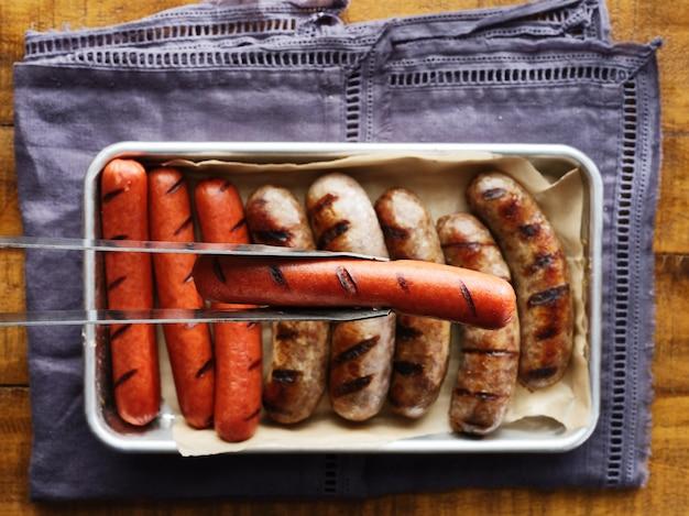 Tenendo hot dog alla griglia con tenaglie sopra il vassoio di carni grigliate
