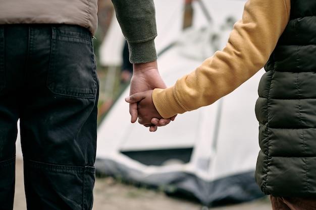 Tenendo la mano del bambino contro il campo di migranti