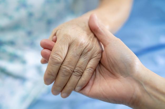 Tenendosi per mano paziente anziano asiatico della donna con amore
