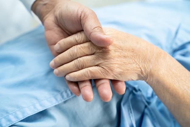 Tenendosi per mano paziente anziano asiatico della donna con amore.