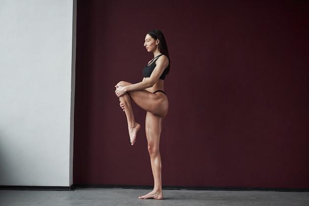 Tenendole la gamba sinistra. bella giovane donna con una bella forma del corpo fitness in posa nella stanza