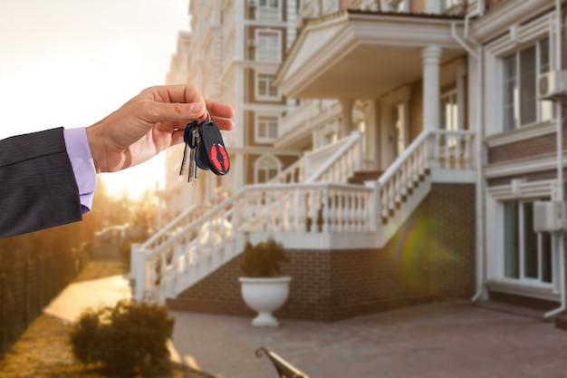 Tenere le chiavi di casa sul portachiavi a forma di casa di fronte a una nuova casa