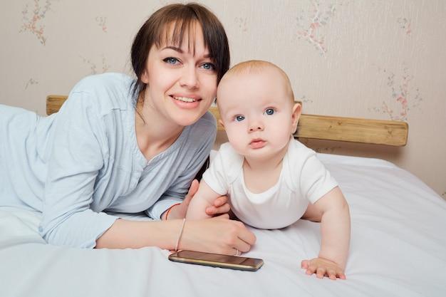 Tenendo piccolo bambino sano bambino e mamma madre e bambino ritratto in primo piano facce felici adorabile bambino mamma e bambino che si divertono al coperto genitori gioia parents