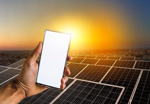 Tenendo un cellulare in uno sfondo di una centrale elettrica a energia solare su un bellissimo cielo al tramonto. spazio per il testo.