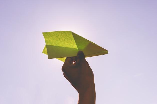 Tenere in mano un aeroplanino di carta durante le vacanze estive