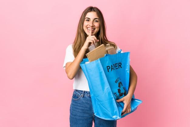 In possesso di un sacchetto di riciclaggio pieno di carta per riciclare isolato gesto facendo silenzio rosa