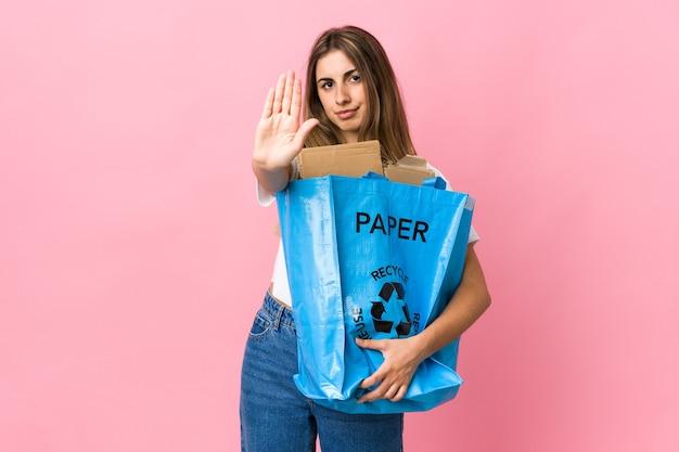In possesso di un sacchetto di riciclaggio pieno di carta da riciclare su rosa isolato facendo gesto di arresto con la mano