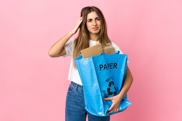Tenendo un sacchetto di riciclaggio pieno di carta da riciclare sopra il rosa isolato infelice e frustrato con qualcosa. espressione facciale negativa