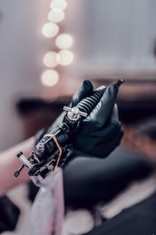Tenendo macchina speciale. maestro del tatuaggio professionale che trasporta macchina per tatuaggi nera piena di inchiostro colorato