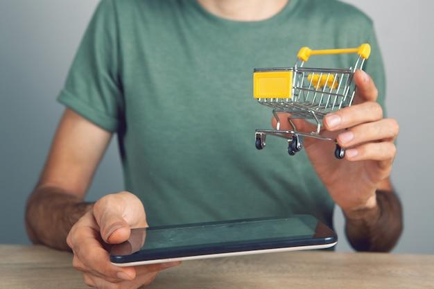 Tenere in mano un tablet con un cestino della spesa