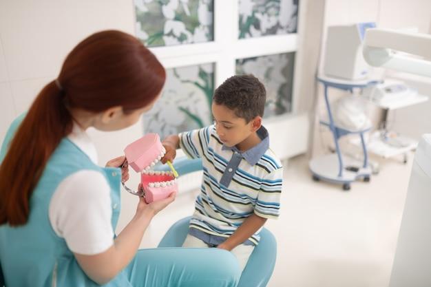 Tenendo il modello dei denti. dentista dai capelli rossi in uniforme che tiene il modello dei denti mentre il ragazzo usa lo spazzolino da denti