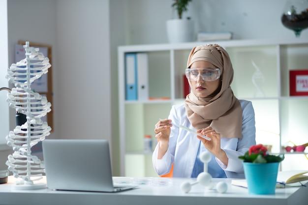 Tenendo la provetta. chimico femminile con gli occhiali che tengono la provetta con un agente chimico