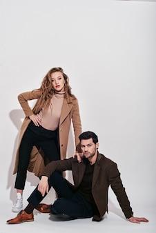 Tenendo stretta coppia attraente e ben vestita in posa in studio