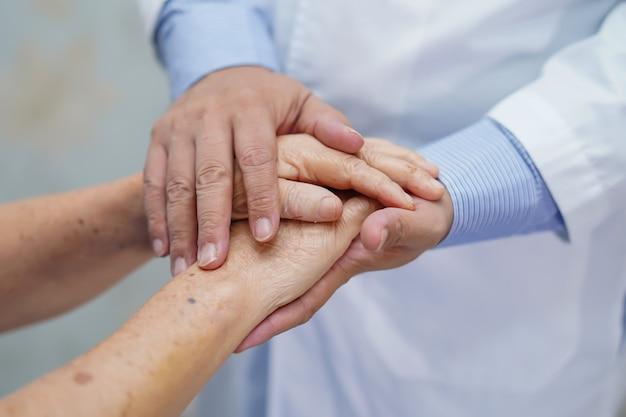 Tenendo le mani commoventi paziente senior asiatico della donna con amore.