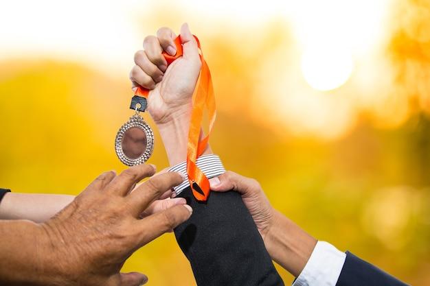 Tenendo i premi della medaglia del vincitore dopo il successo con la sua attività.