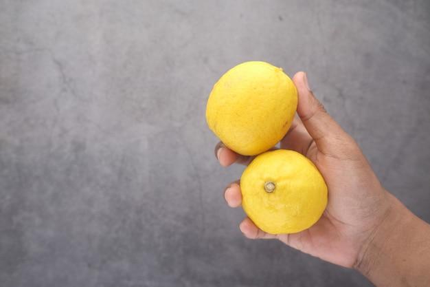 Tenendo il limone giallo su sfondo nero