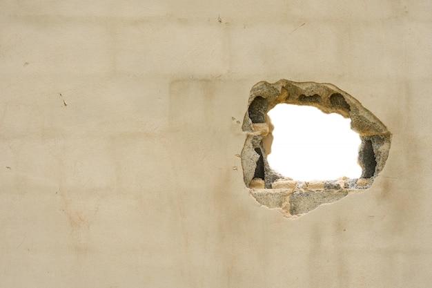 Foro nel muro concreate con sfondo bianco e spazio vuoto
