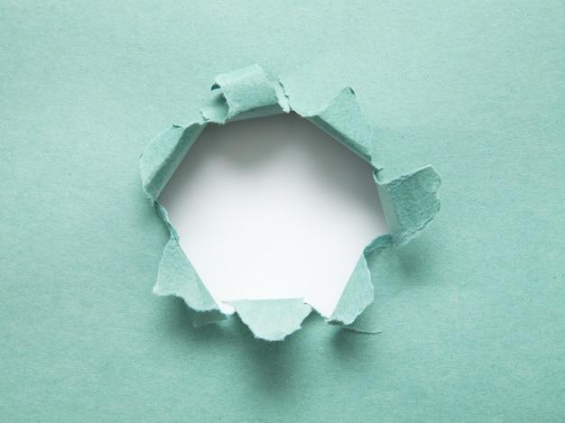 Un buco nella carta con i lati strappati. carta strappata. con spazio per il tuo messaggio