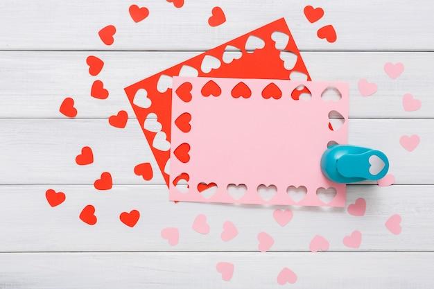 Perforatore a forma di cuore, taglia e incolla, carta artigianale e strumenti fai da te su legno bianco