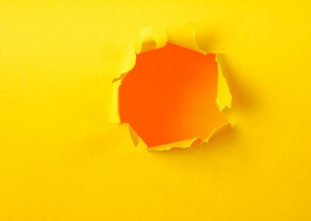 Foro di carta gialla strappata. copia spazio
