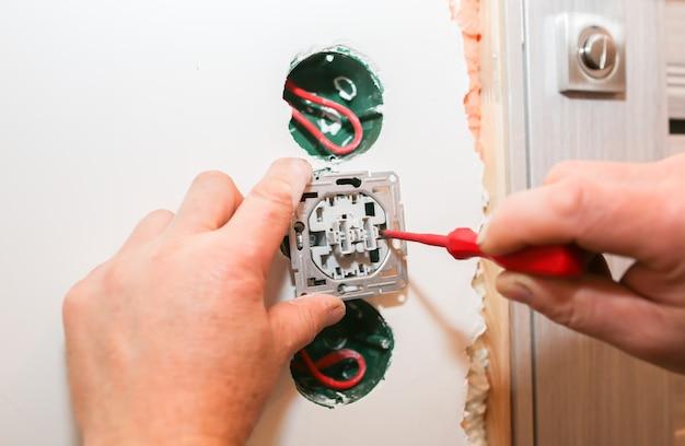 Fori nel muro con fili colorati per interruttori presa. uomo che installa elettricità. ristrutturazione lavori di riparazione di manutenzione nell'appartamento. restauro al chiuso.