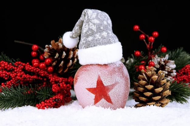 Mela delle vacanze con stella smerigliata nella neve su sfondo nero