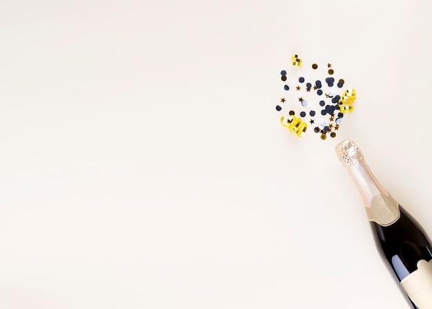 Attributi di vacanza. bottiglia di champagne e coriandoli a forma di schizzi per il nuovo anno su sfondo beige