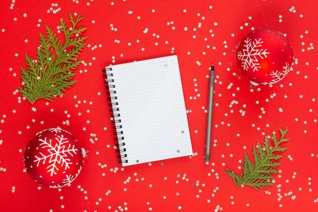 Sfondo vacanza, palle di natale con fiocchi di neve e ramoscelli di thuja su uno sfondo rosso con stelle glitter argento, blocco note a spirale aperto e penna, vista piana laico, dall'alto